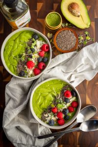 Two keto avocado matcha smoothie bowls with fresh berries and chia seeds flat lay
