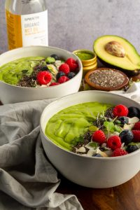Two keto avocado matcha smoothie bowls with fresh berries and chia seeds, avocado, chia seeds and MCT Oil in the back ground