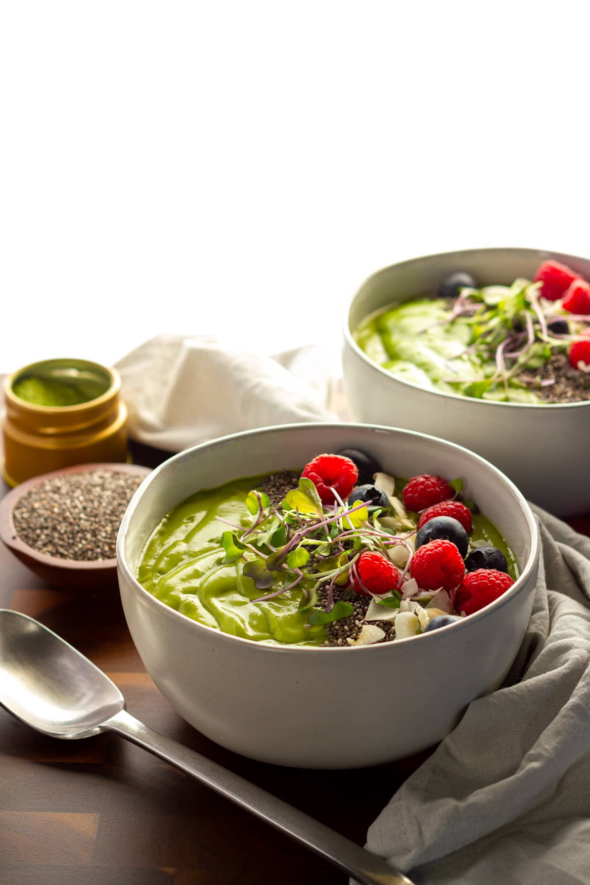 Two keto avocado matcha smoothie bowls with fresh berries and chia seeds