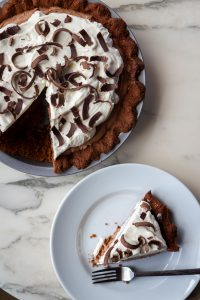 A rich keto chocolate French silk pie with dark chocolate shavings on top.