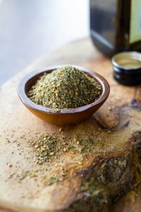 Small bowl of za'atar spice with olive oil in the background.