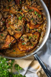 Pan of paprika seasoned pork chops in a mushroom garlic cream sauce