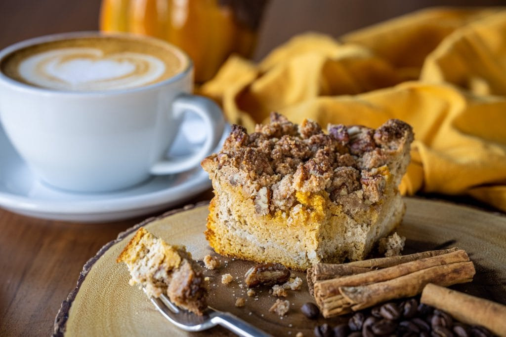A slice of crumbly Keto Pumpkin Spice Coffee Cake with a warm latte